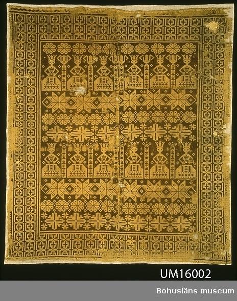 """Vävnad av gulbeige och brunt ullgarn. Mönstrad dubbelväv. Mönstret består av en bård med kors i rutor och en mittspegel med mönsterfigurer i rader; runduddig stjärna, jungfrur (bibelns visa jungfrur), stjärnor, fåvitska jungfrur (fåvitsk=tanklös) och geometriska figurer med """"munkabältesstjärnor"""". De visa jungfrurna är de översta.  Inga fransar, fållar på kortsidorna. Enligt tidigare katalogisering Mönster: """"Krönta brudar"""". Vävnaden är avbildad i """"Textilier från Bohusläns museum"""". Om detta är den vävnad Brudarne (Krönta brudar) som tas upp i två olika inventarieförteckningar över Göteborgs och Bohusläns Hemslöjdsförenings föremål (se museets arkiv, mapp om Bertha Kleberg mm, placering: 18.01.2.) så är den skänkt till Hemslöjdsföreningen av lantbrukaren Alfred Larsson, Källsby, Jörlanda innan 1935 då den äldre av förteckningarna är gjord.  Finnväv användes oftast att pryda väggarna med till fest, men kunde också läggas över den uppbäddade sängen eller användas som bordtäcke vid husförhör. (Berg 1991, sidorna 236 och 242). För ytterligare uppgifter om givaren se UM016001 Mycket sliten. Flera hål rakt igenom, ytterligare hål i bruna vävlagret. Flera lagningar. Blekt. Uppsydd mot linnetyg inför utställning."""