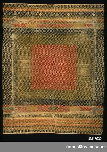 Täcke av två våder, ihopsytt med längsgående söm. Vävt i solvad upp hämta med delvis inplockat mönster (flera olika trådar används över vävbredden och snärjs om varandra där de möts). Det yttäckande mönstret som uppstår genom solvning och trampning är mycket små romber. Den egentliga mönstringen uppstår genom att ränder, fält och mönsterfigurer vävs med mönsterinslag av olika färger. Bottenväv i tuskaft av beige bomullsgarn. Täcket har ett mittfält bestående av en röd mittruta (vävd med rött  och ljusrött garn) omgiven av en gråtonat gulgrön ram och utanför den  en svart ram. Över och under mittfältet finns bårder i beige, gråtonat ljusblått, svart, gulbrunt, ljusrött och gråtonat ljusgult. Mönstren i bårderna är ränder och inplockade pilformade mönsterfigurer och  romber. Rester av korta öglade fransar finns längs långsidorna, dels av mönsterinslaget, dels av påsytt ullgarn i olika färger (längs den svarta mittramens sida.) Vid ena kortsidan märkt ?MD 1854 (troligen CMD) med korsstygn i ljusrött lingarn.  Solvad upphämta uppkallades efter hur många skaft som användes till väven, dock är litteraturen oklar vad gäller om bottenskaftens antal ska räknas in. Idag lärs solvad upphämta ut under namnet smålandsväv.  Mittrutan kallades ibland prästruta, för där skulle prästen lägga bibeln vid husförhör. Ordet täcke användes förr om en vävnad som användes att täcka över en möbel, såväl säng som bord.  Slitmärken och lagningar som bildar en fyrkant på detta täcke talar om att det troligen använts till duk på ett bord. Mycket slitet, mönsterinslaget bitvis bortslitet. Lagningar (stoppningar) ca 13 cm in från kanten på fyra ställen. Ett stort hål bredvid en sådan lagning. Fläckigt.  Litt; Berg, Kerstin, Selma Johansson - väverska och hembygdsforskare i Södra Bohuslän, Skrifter utgivna av Bohusläns museum och Bohusläns hembygdsförbund Nr 41, Uddevalla 1991, sid 178-186.  Lychou, Kerstin, Hemslöjd och folkkonst i Bohuslän, Warne förlag AB, Partille 1996, sid. 156-160.  Sekora, A