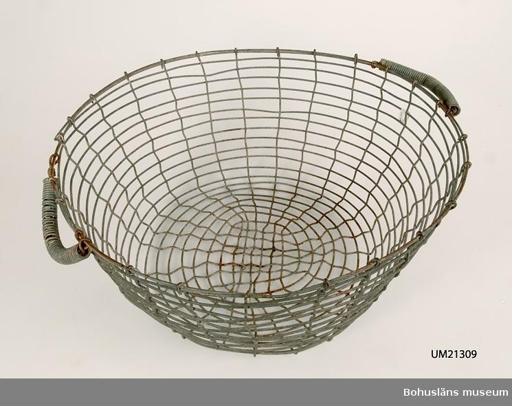 Rund korg vilken är svagt konande nedåt. Två ledade bärhandtag omvirade med ståltråd. Korroderade. Mått på den andra korgen: L 53,5, B 55, H 22 cm
