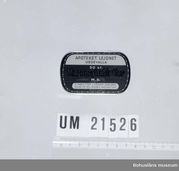"""594 Landskap BOHUSLÄN 394 Landskap NÄRKE  Burkens lock är märkt med: """"Apoteket Lejonet Uddevalla"""", """"50 st Magnecyltabletter M.B.2 tabletter 3 gånger dagligen eller efter läkarens ordination"""".  UMFF 28:12"""
