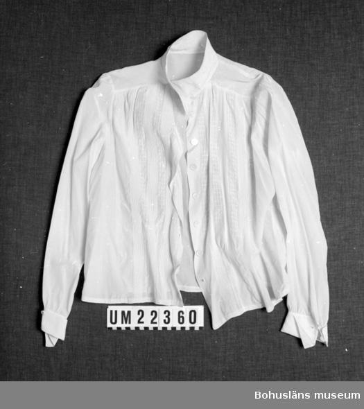 410 Mått/Vikt ! ÄL 42, KH 3,5 CM 594 Landskap BOHUSLÄN  Blusen är vit. Framtill små sydda veck. Sex pärlemorknappar för knäppning fram och en i vardera ärmen samt en tryckknapp vid linningen.  UMFF 101:9