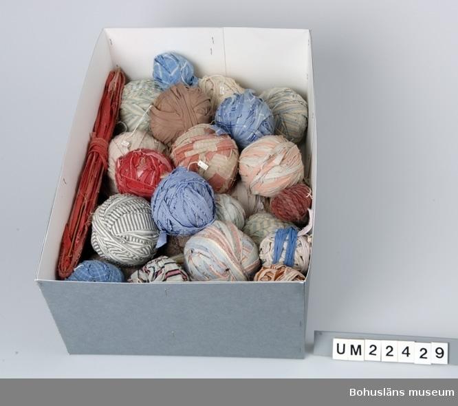 Funktion: som inslag vid vävning av trasmattor. 65 nystan i olika färger, klippta av utslitna kläder. Vikt 9,8 kg. Även en mattsticka med pålindade röda mattrasor finns under samma nummer.