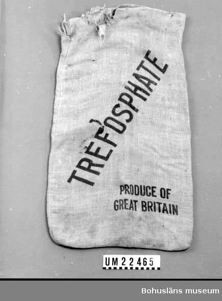 """412 Förvärvstillst STORA HÅL OCH REVOR VID ÖPPN. 594 Landskap BOHUSLÄN  Rektangulär, beige säck. På ena sidan, svart text: """"TREFOSPHATE PRODUCE OF GREAT BRITAIN"""". Säcken är ursprungligen använd till gödningsmedel. Tyget har hål.  Omkatalogiserat 1996-12-30 GH.  UMFF 118:8"""