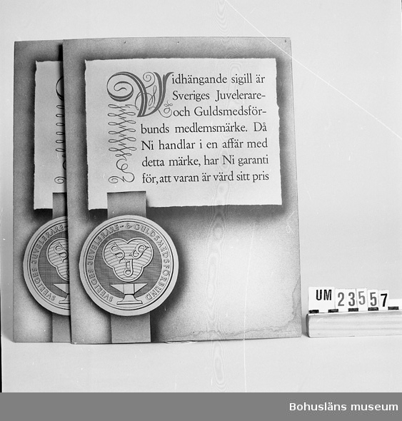 """471 Tillverkningstid 1935-1955 594 Landskap BOHUSLÄN  Reklam för guldsmeder: """"Vidhängande sigill är Sveriges Juvelerare- och Guldsmedsförbunds medlemsmärke. Då Ni handlar i en affär med detta märke, har Ni garanti för att varan är värd sitt pris."""""""