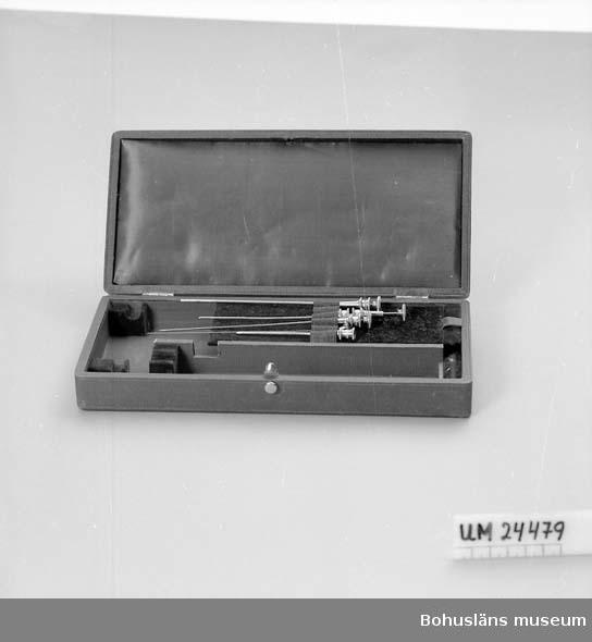 """594 Landskap BOHUSLÄN  Svart låda med lila """"siden"""" och sammetklädsel innuti. I lådan ligger 5 st metallstickor.  De är fastsatta under ett lila resårband. Med stor sannolikhet nålar för lumbalpunktion."""