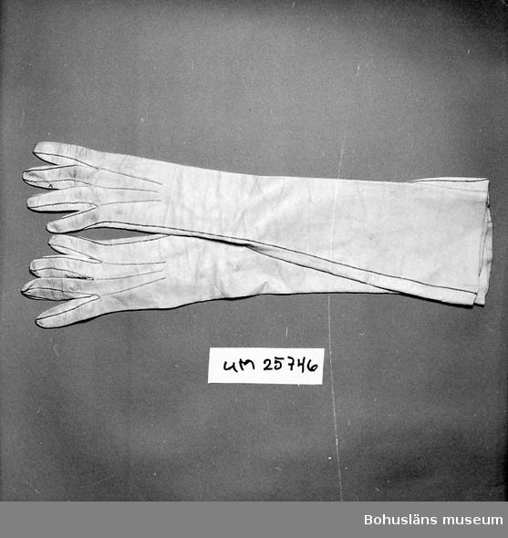 Långa vita glacehandskar, nu något gulnade. På handens insida 11 cm slits knäppt med 3 pärlliknande knappar å vardera handske. Samtliga bevarade. Mått kragens bredd 13,5 cm. Bristningar och lagringar mellan några fingrar. Använd till brudklänning UM025742. Personuppgifter se UM025730 och UM025739.