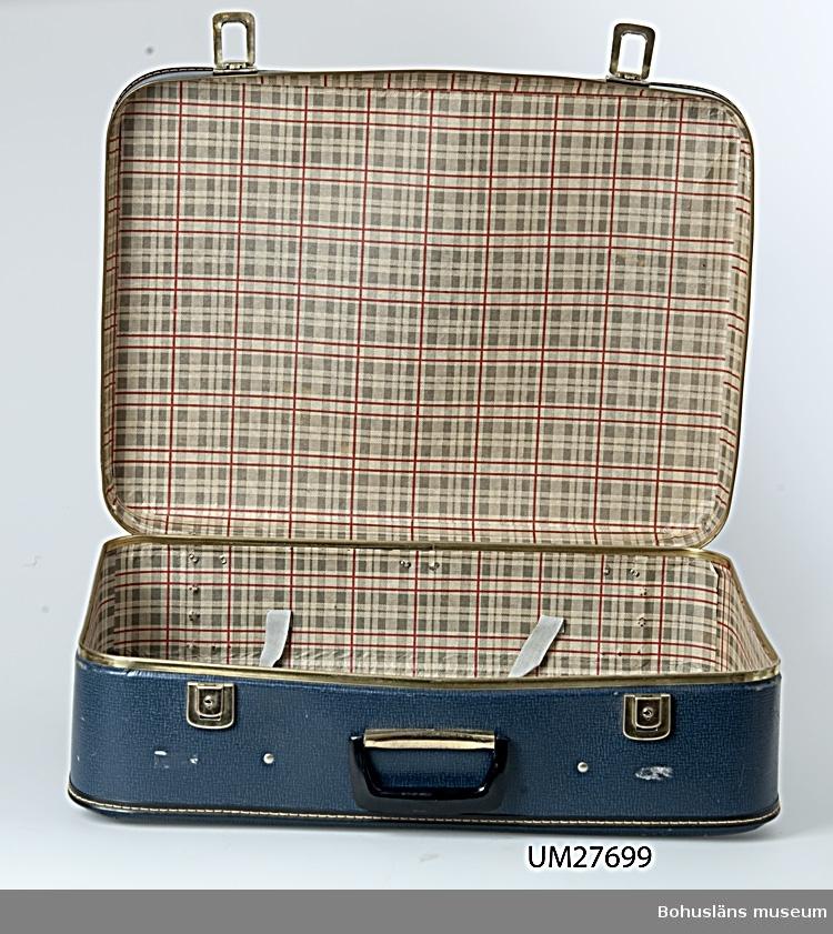 Blå resväska av styv papp, på utsidan präglad i yta liknande läder. Låsbara knäppen av guldmetall på långsidan. Handtag av svart plast. Lockets och underdelens kanter förstärkta med metallskena. Invändigt fodrad med rutigt tyg i  rött och grått  på beige  botten.  I locket två tygremmar med spännen att hålla fast innehållet.  På utsidan klisteretikett i gulpapper med tryckta texten:  ABC FABRIKERNA KUNGÄLV SWEDEN   För ytterligare upplysningar om  insamlingen, utställningen 2001 och litteratur, se UM27670.