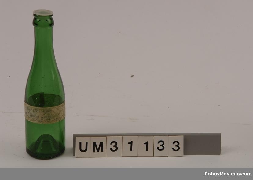 Bryggeriflaska, ca 20 cl., i grönt glas med plastkork. Påklistrad tejpremsa där Bernhardson skrivit: Flaskpost... ... ...  Funnen som vrakgods i Bohuslän?  Bernhardson beskriver barnens vrakletning i boken  Bohuslän - från Wämmer ock Kräppe  s. 128: Ätter e hale västa å massa lanfall brogga ongane sprenge langs strännena å röra i tanga - de leda ätter granne bôttlar mä konsti korkar å färger, de sanka på sånna. (Efter hård västanvind och högvatten brukade barnen springa längs stränderna och sparka i tången. Barnen sökte efter vackra buteljer med olikartade skruvkorkar och färger. Man samlade på sådana flaskor). Tidsbild 1920-talet  Litt: Bernhardson, C. G.: Bohuslän - från Wämmer ocH Kräppe. Uddevalla 1985.  För ytterligare upplysningar om förvärvet, se UM31100.