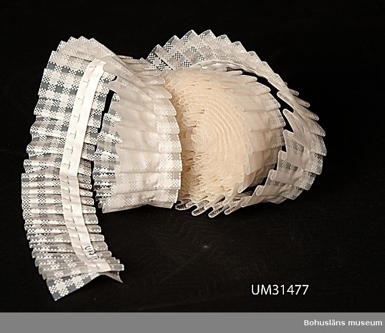 Hyllremsa av genomskinlig plast med vitt rutmönster. Smalveckad med ett vitt plastband, fastgjutet och präglat på baksidan. Oanvänd.  Föremålet har använts av familjen Abrahamson i deras sommarstuga i Sundsandvik, byggd 1939. För ytterligare upplysningar om förvärvet, se UM031385.
