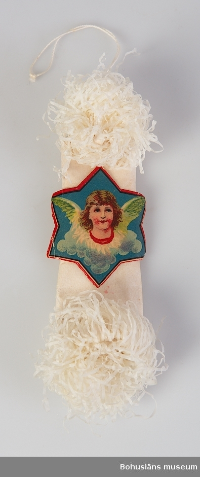 """Avlång julgransdekoration med krusade ändar avsedd att hänga i julgran. Bokmärke i form av sexuddig stjärna med ängel klistrad på mittdelen. Vitt bomullssnöre för upphängning i ena ändan. """"Rosor/chrysantemum""""-modell - jämför UM024229"""