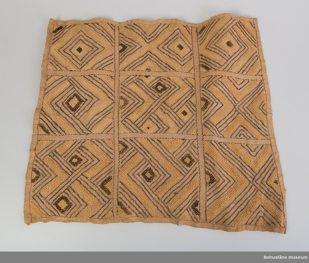 """Kontinent: Afrika Enligt litteraturen är vävnader av detta slaget utförda av stammar som levde i området Kasai i södra delen av forna Belgiska Kongo, senare Zaire. Man pratar om det på 1600-talet bildade Kuba-riket. Ett folk inom Kuba, Shoowa-stammen, var kända för sin mycket speciella och högt skattade broderiteknik. Det var männen i Shoowa-stammen som vävde, medan kvinnorna broderade de geometriska mönstren.  Rombiska former broderade i gult och brunt mot ljusare gulvit tuskaftsbotten. Flossakaraktär på delar av broderiet. Mönstren indelade i nio kvadratiska fält. Stadkanterna på vävnaden är vikta och fållade mot framsidan med förstygn; likaså fållarna i längdriktningen.  Litt.: Artikel i Hemslöjden nr 4/1990, """"Den saboterade symmetrin"""", Olle Nessle, s. 14-15.  Uppgifter om E. Göransson i Knut Adrian Anderssons katalog samt historik om samlingen: Se UM61.03.001"""