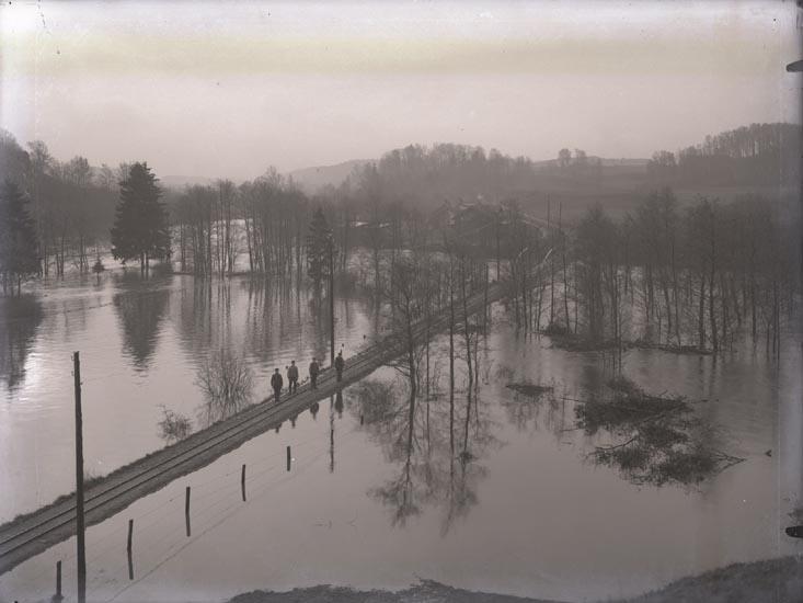 """""""Öfversvämning av lilla Järnvägen vid Bajan Munkedal.""""  """"Banchef Svensson- Svensson J:r- okänd- okänd. I bakgrunden Nils Anderssons hus (fotografen har stått på Hede mark)."""""""
