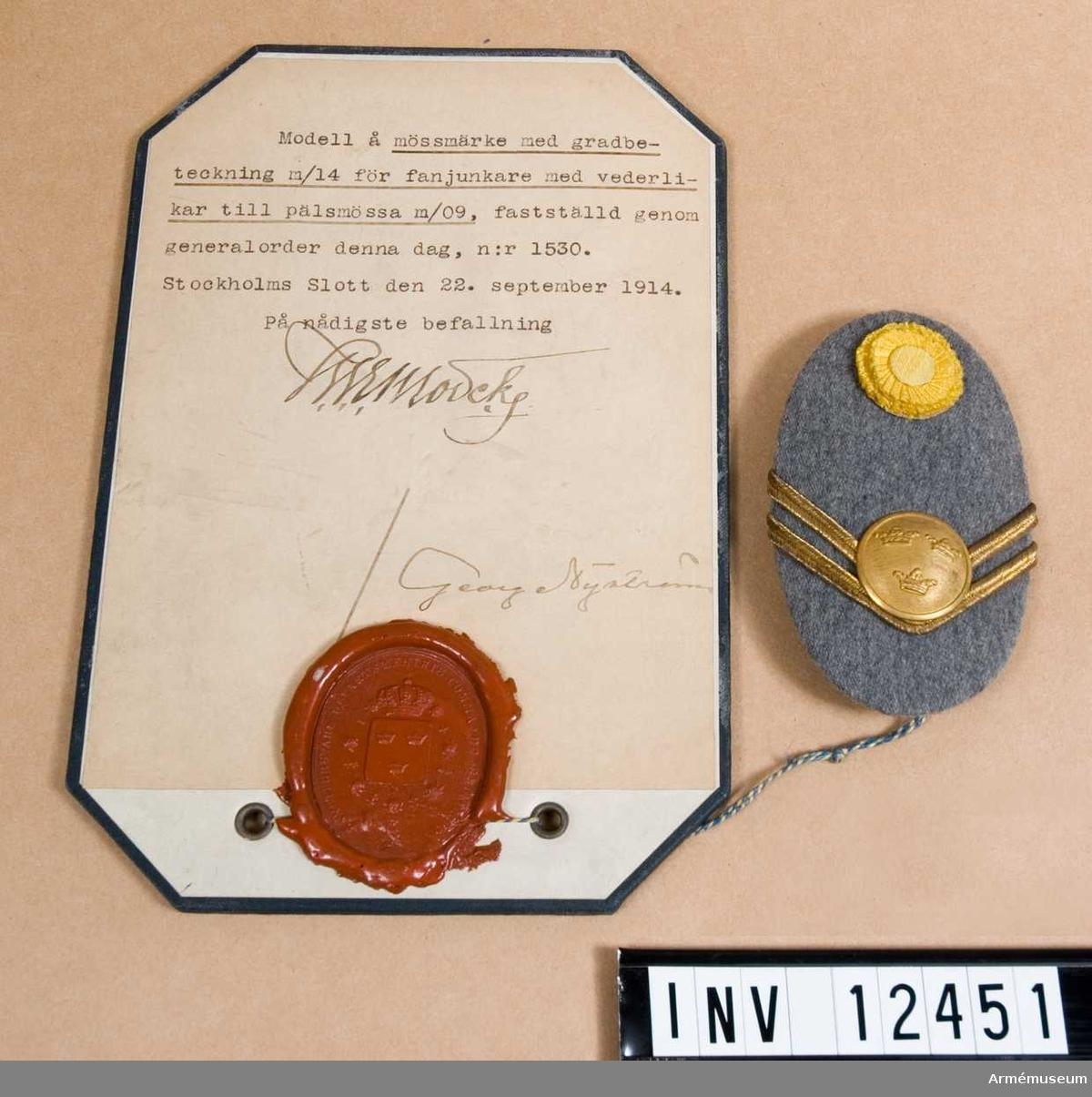 Grupp C I. Modell på mössmärke med gradbeteckning m/1914 för fanjunkare med vederlikar till pälsmössa m/1909.  Från intendenturens modellkammare.