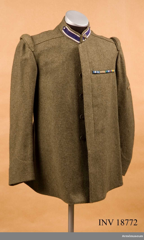 """Grupp C I. Ur uniform för manskap vid infanteriet, Italien. Av grönblått kläde. Enradig med 5 kakifärgade knappar som knäppes inuti. På rockens baksida 2 inskärningar som knäppes med 2 knappar vardera. På båda axlarna finns två avlånga, vadderade kuddar för att bättre hålla gevärsremmen på axeln. På rockens bröst finns 4 medalj- och ordensband. Foder av vitt tyg med två inre sidofickor; den ena med knapp för första hjälpen, sanitetspaket. På fodret stämplar """"C Tabia"""", """"1929"""", """"OM"""". """"Torino"""" =Parma- brigadens förläggningsort. Knappar 5 st av ben, kakifärgade, på bröstet och 4 st på baksidan vid inskärningarna. Krage, upprättstående, av samma kläde. På kragens båda sidor finns fastsydd """"spegel"""" av blå-vitt silkesband med små knappar av vit metall. Blå-vit färg är känneteckensfärg för Parma- brigaden (infanteriregementen N 49 och 50). På """"spegel"""" finns femuddig stjärna av vit metall- officers känneteckensmärke (för meniga av vitt kläde). Kragen stänges med 2 hyskor och hakar. Ärmuppslag av samma kakikläde i vinkelform. På vänstra överarmen, liten silvergalon (efter gammal museum- etikett: den galonen angiver antalet gånger som soldaten sårats i fält. LITT  Handbuch der Uniformkunde, prof Richard Knötel, Hamburg 1937, s. 234, 235. Redan år 1908 provades kakifärgade uniformen i italienska armén; under världskriget år 1915  infördes kakiuniform i form av en fältblus med ärmuppslag i vinkelform och uppstående krage med olika färgade silkesband på kragen (brigadens känneteckenfärger). Brigaden parma har  """"spegel"""" av blått silkesband med vita smala ränder på sidorna. Till Parmabrigaden hör infanteriregementen N 49 och 50. Armeen Album II. Die grauen Felduniformen der Italienischen Armee. Verlag M Ruhl. Sida 7. Infanterie. Felduniform. Vapen- rock av kakifärgat kläde, utan knappar. På kragen färgad """"spegel""""; för var brigad olika färg. På """"spegeln"""" finns, för att skilja officerare och meniga, olika femuddiga stjärnor av vit metall och för meniga av vitt kläde. Bilaga: Die unte"""