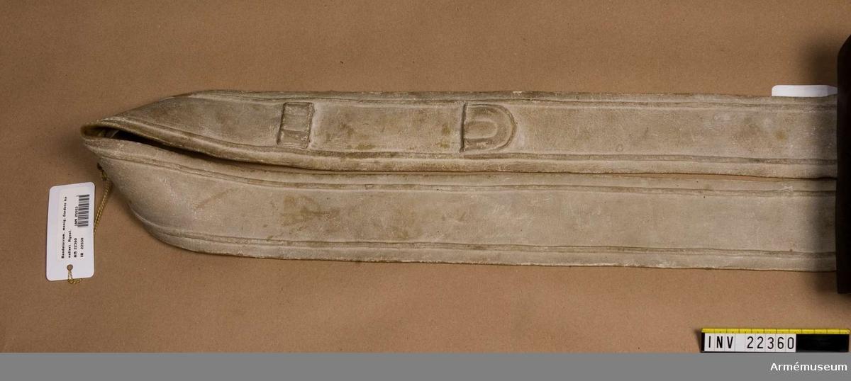 Grupp C I. Ur uniform m/1820-40 för menig vid Livgardet till häst, Andra regementet 1. Gardets kavalleridivision. Av vitmålat läder med inpressad rand utmed kanterna. På kortsidorna 2 smala remmar för remmens fastgörning vid kartuschens 2 spännen.
