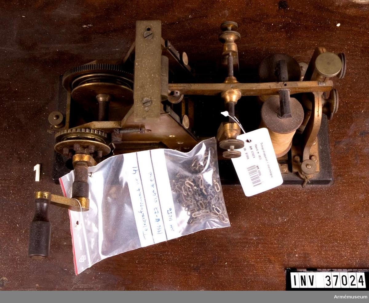 """Grupp H I.  Skrivapparat uppbyggt på en ebonitsockel. Frammatningen av pappersremsan sker med ett loddrivet verk. """"Skriften"""" på remsan sker med ett metallstift som trycker med pappret i ett spår på den underliggande metallvalsen. Apparaten är märkt """"n:o 41 W. Gurlt & Co. Berlin""""."""