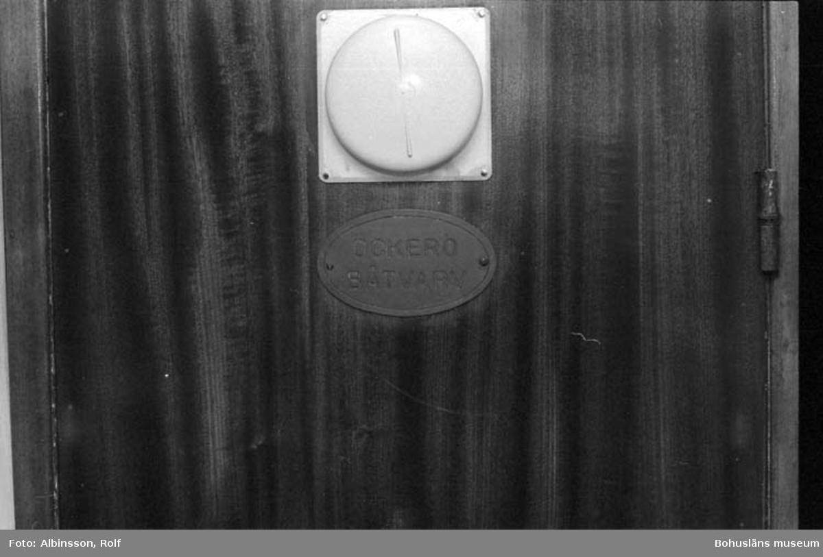 """Enligt fotografens noteringar: """"Mässingsplatta på dörren, """"Öckerö båtvarv"""", där byggdes Äran.""""  Fototid: 1996-04-03.  1996-04-04.  1996-04-05."""
