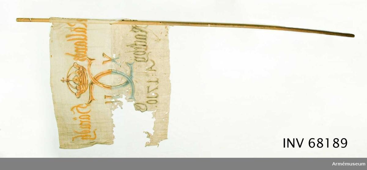 Duk: Tillverkad av enkel vit linnelärft, sammankastade med kastfåll åt utsidan. Vertikala ytterkantsfållen lagd åt utsidan. Fastsydd runt stången.  Dekor:  Målad endast på dukens insida, dock är kronan och namnchiffret ifyllt på utsidan, i mitten Carl XII:s namnchiffer krönt med sluten krona, dubbelt C, på ömse sidor om detta X-II, i den övre våden i gult och brunt i den nedre våden i blått och svart.   Text på ömse sidor om chiffret, upptill i gult och nedtill i svart. Under chiffret text i svart.  Stång: Tillverkad av trä.