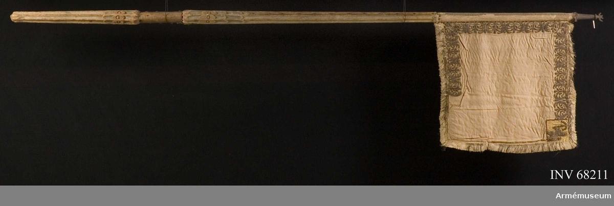 Duk: Tillverkad av dubbel, vit sidendamast; duken nästan helt borta, konserverad med shantung i två lager (Pietas nr 33 1910). Duken fäst vid stången med en rad tennlickor på en drejad guldfrans.  Dekor:  Broderad i reliefbroderi, läggsöm. Runt dukens kant en bård med kandelabermotiv. I yttre, övre hörnet Smålands vapen, ett dubbelsvansat lejon förande ett spänt armborst (Resten av dekoren saknas.), underkantens bård något defekt.  Frans:  Dubbel, av vitt silke.  Stång: Tillverkad av trä, kannelerad, gulmålad. Vid greppet karvsnittsdekor. Greppet järnbeslaget. Spets av järn, avbruten.
