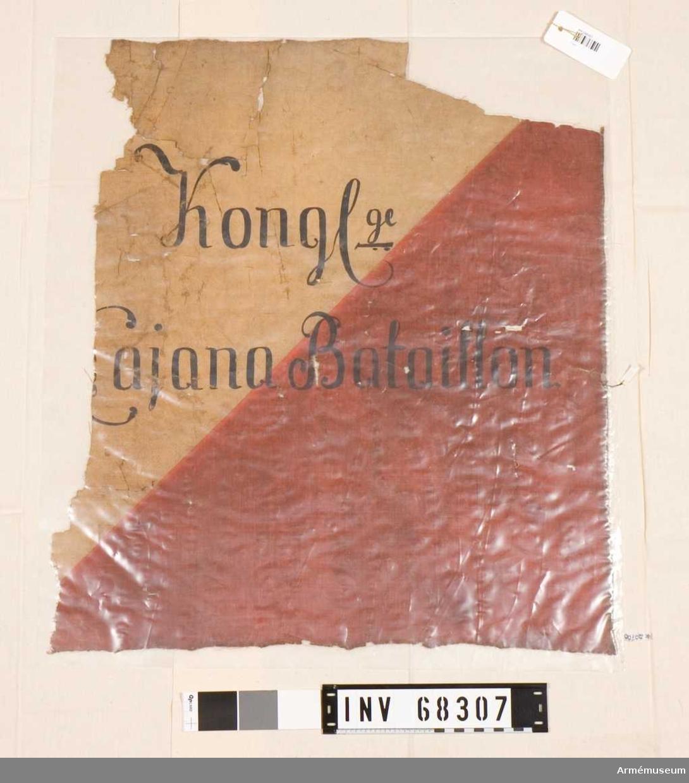 Skadad kvartersfana, insydd i plastficka. Sydd i två delar, den övre i gult tyg och den nedre i rött. Text påförd.  Liknande AM.068131