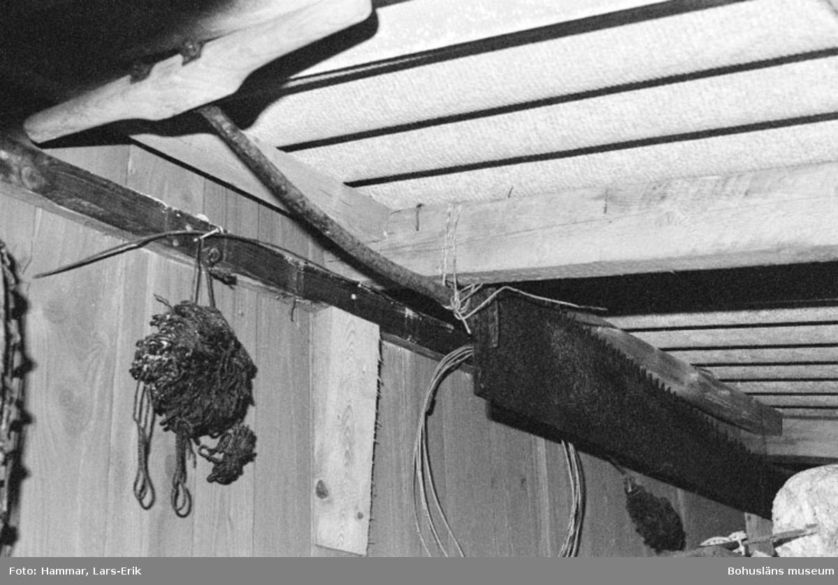 """Motivbeskrivning: """"F.d varv i Skredsvik, interiör från tillbyggnad till virkesmagasin.  På bilden syns en långsåg upphängd vid taket."""" Datum: 19800717"""
