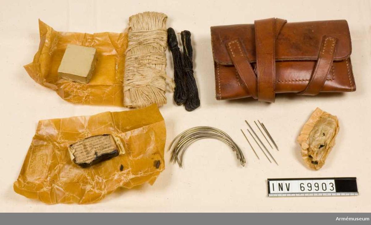 Sylväska av läder innehållande segelgarn, becktråd, nålar, nubb, beck samt okänd substans i form av en kloss.