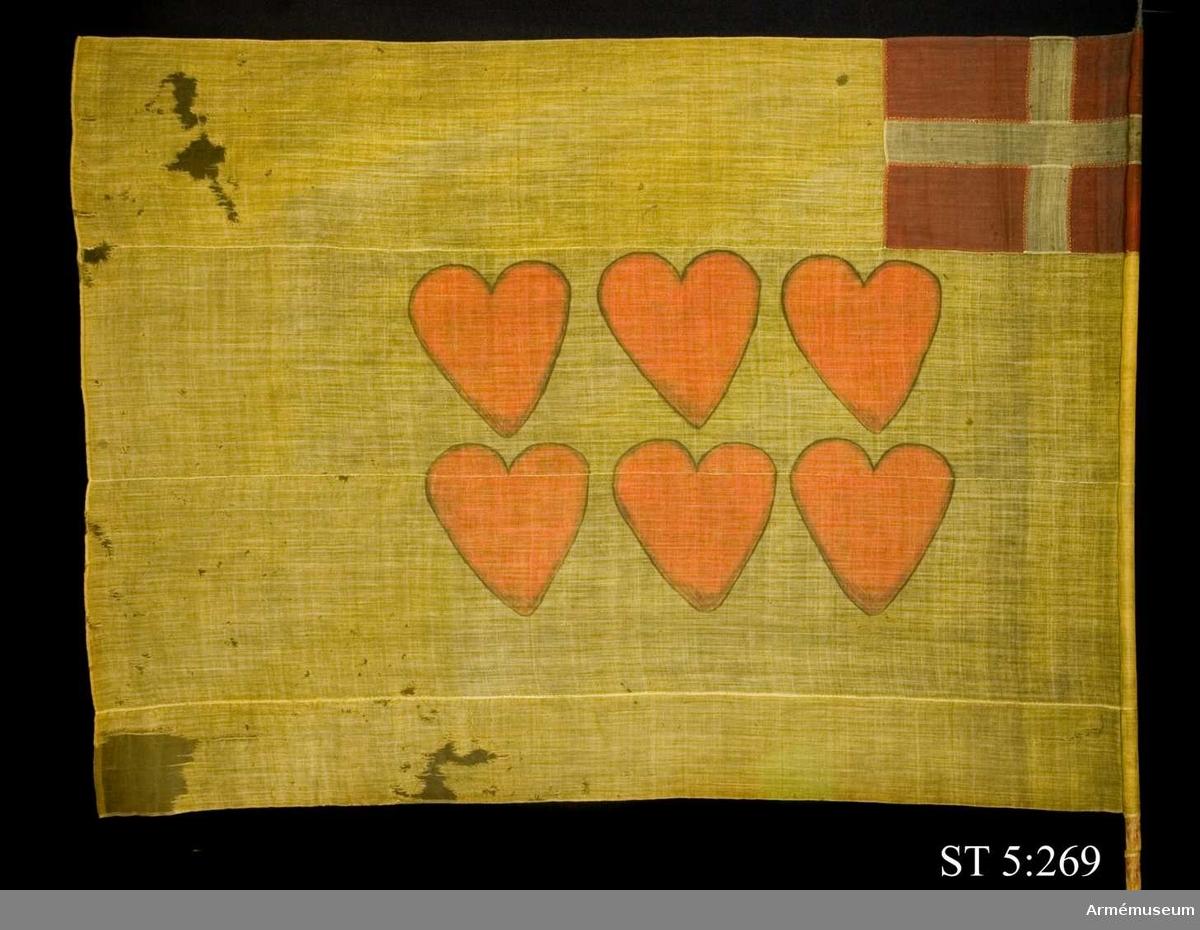 Ylleduk med infällning och målning.  Upptill vid stångsidan infälld Dannebrogen . Mitt på duken målat sex hjärtan i två rader.