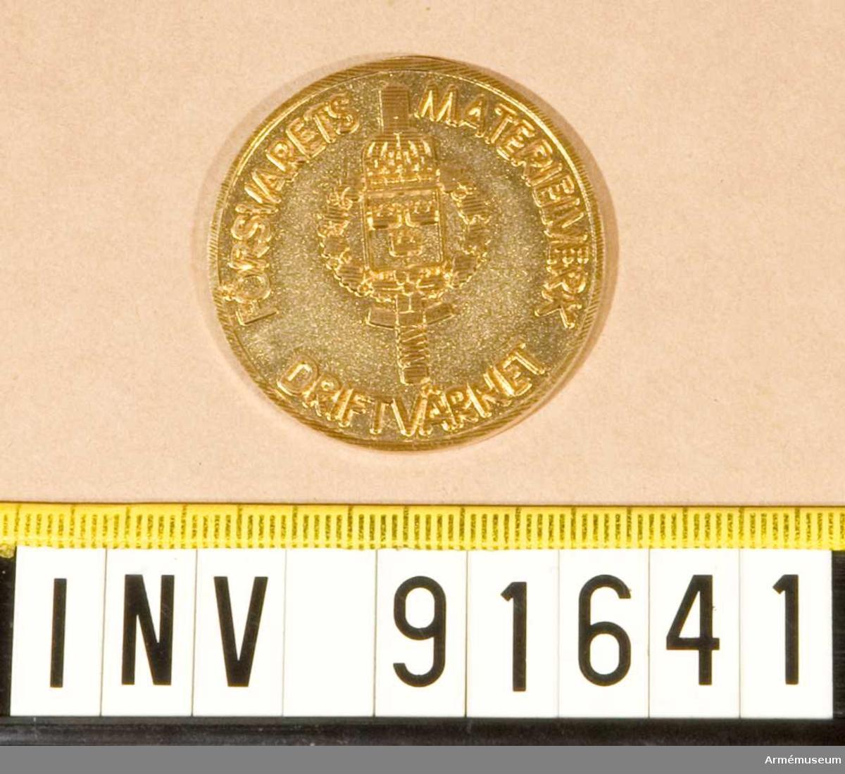 """Mynt i guld. Framsida: FMV:s emblem och texten: """"FÖRSVARETS MATERIELVERK DRIFTVÄRNET""""."""