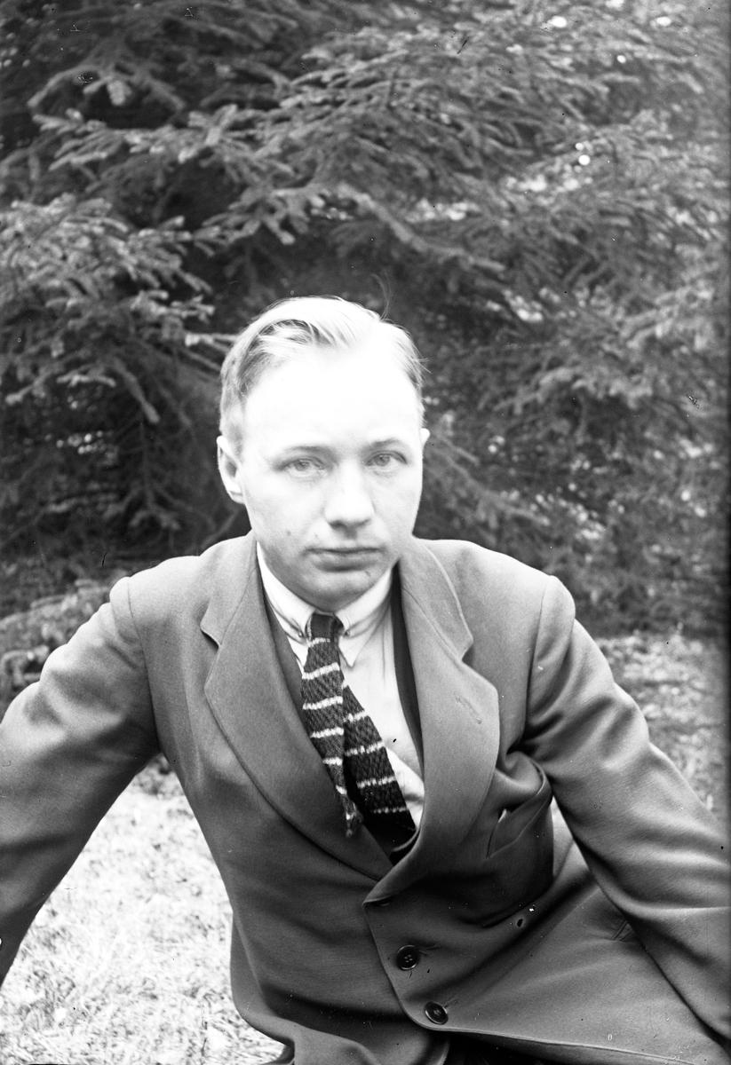 Porträtt av fotograf Gustav Andersson från Jönköping, i bakgrunden syns granar.