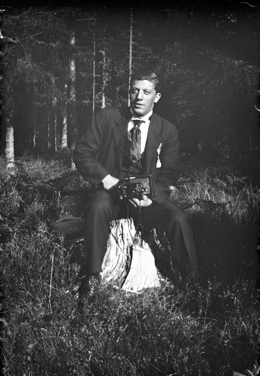 En man med kamera i knät sitter på en stubbe i skogen vid Lungkliniken i Eksjö.