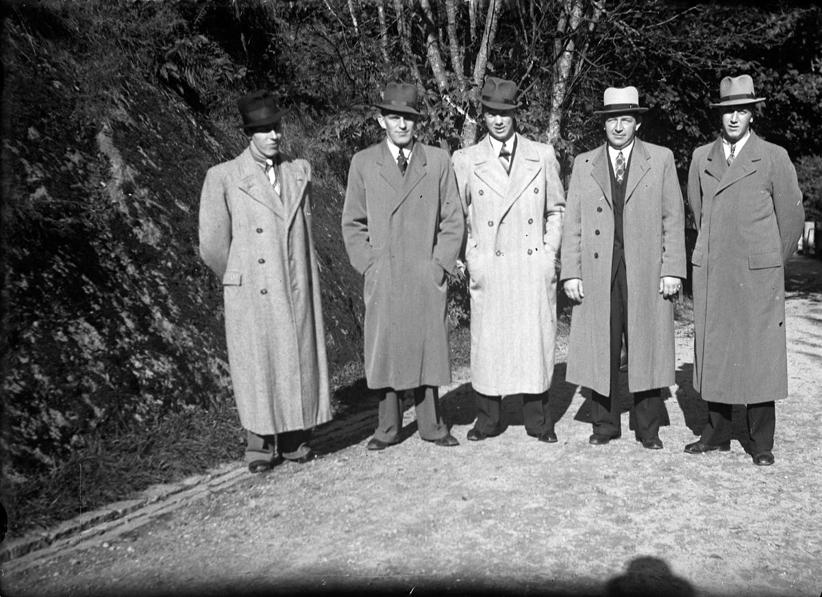 Fem män klädda i rock och hatt står på en väg, vid sidan syns en bergssluttning och träd.