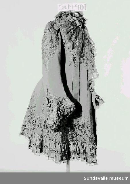 Svart damkappa av ylle med spetsar, samt genombrutet nättyg och snörmakerier. Knäppes med hakar och hyskor, samt knytband frampå i midjehöjd. Etikett i nacken med texten 'H. DE Thanch Höckendorff Kungsträdgården 20, Stockholm'. Kappan har tillhört Zelma af Sandeberg, född Kinnman 1843; gift med rådman Svante Karl Otto af Sandeberg, Sundsvall; mormor till Astrid Sundblad, född 1895.