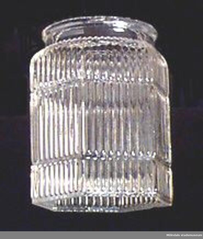 Sexkantig ofärgad lampskärm i pressat glas. På utsidan smala lodräta räfflor. Rund hals. Skärmen upphittades i jorden på givarens tomt Forsåkersgatan 57.