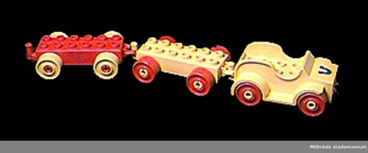 Öppen gul leksaksbil med två påkopplingsbara vagnar.Modulerna specialdesignade delar av Duplosystemet. Se MM02361.MM02362:1 bil med en blå hästsko på motorhuven.MM02362:2-3 släpvagn. Fästet för att koppla i dragkroken, har lossnat på MM02362:3.Katrinebergs daghem var ett kollektivt daghem.Gåva av Katrinebergs daghem.