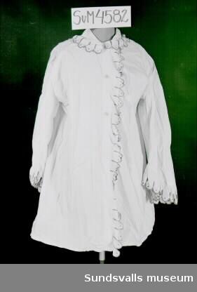 Skjorta i naturvitt bomullstyg med långa vida ärmar som är rynkade mot axeln. Plattsömsbroderi och langettsöm i rosa och vitt på volang vid manschett, krage och mitt fram. Knäppning fram med två tygklädda knappar.