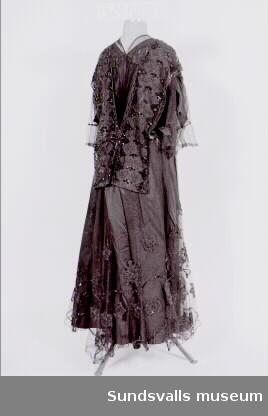Svart tvådelad klänning. Klänningslivet (SuM 4836:1) är sytt i lager med siden och tyll och broderat med pärlor och paljetter. Vitt foder med stödskenor. Knäppning fram med hakar och hyskor. Livet är 63 cm långt. Kjolen (SuM 4836:2) är sydd i två lager och broderad med pärlor och paljetter. Tryckknappsknäppning. Kjolens längd är 90 cm. Observera att plagget är felaktigt märkt på båda negativen.