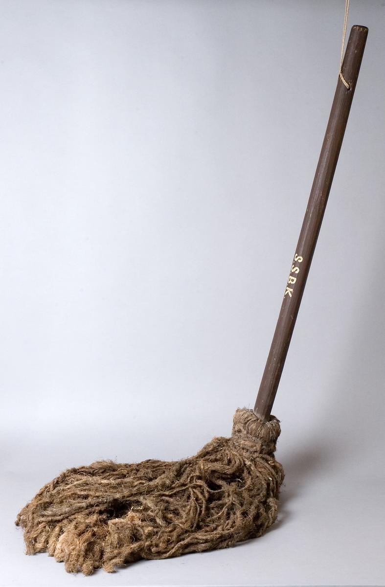"""Svabb tillverkad av trä och hampa. Svabben har runda hyvlade handtag målade i mörkbrunt. Ett hål är borrat genom handtaget och där är ett snöre trätt, knutet till en ögla. Själva svabben består av en lång """"tofs"""" av hampgarn, fäst i ena änden med en genomgående träplugg."""