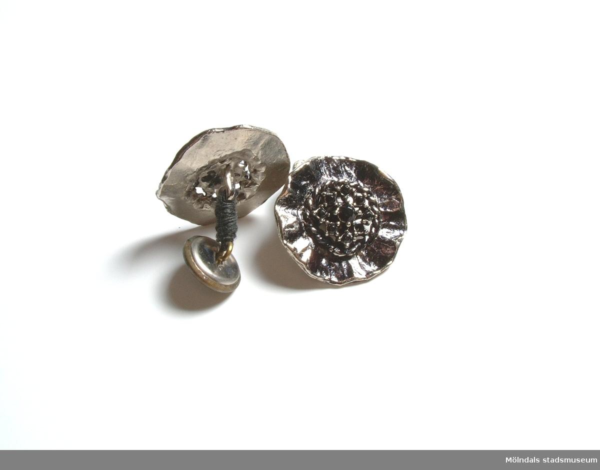 Manschettknappar tillverkade av var sin stor blomliknade knapp i svart och silver med svarta stenar i mitten. Knapparna är hopfästade via en träns med en mindre metallknapp.Givaren/användaren/tillverkaren konstruerade dessa manschettknappar för att passa till en speciell blus och för att ha originella detaljer i sin klädsel.