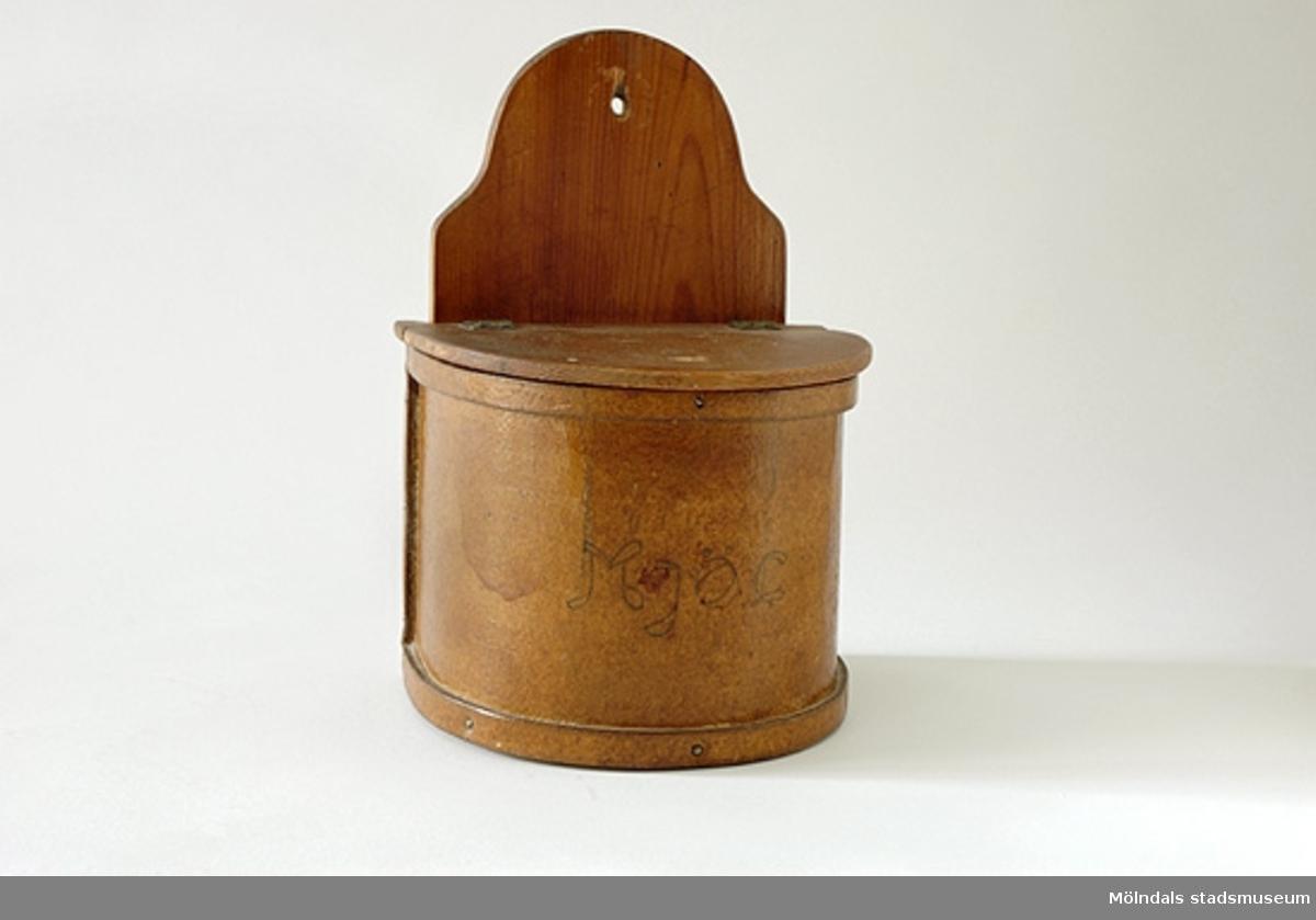 Handtillverkad behållare för mjöl med uppfällbart lock. Hål för upphängning.Handskriven text: Mjöl.
