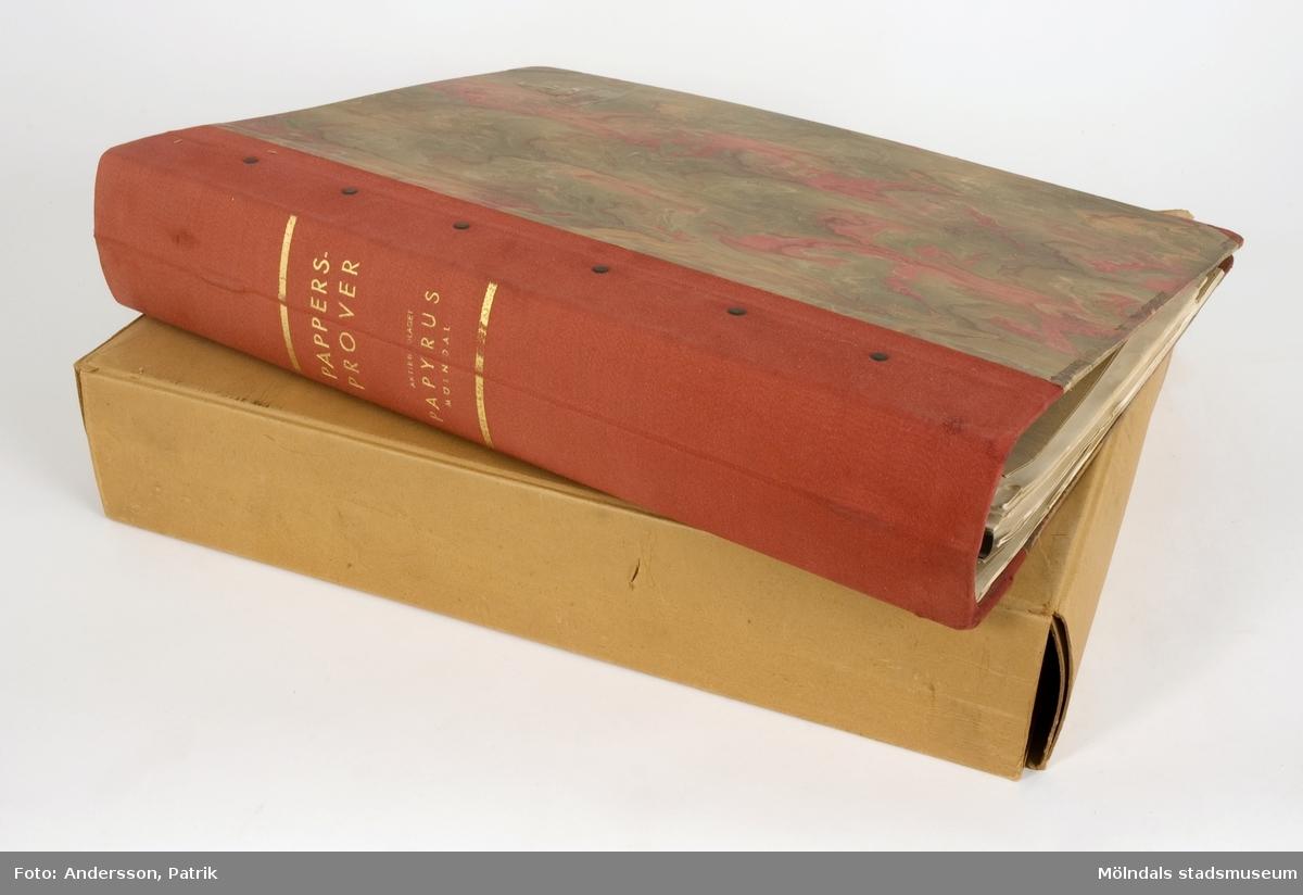 """Pärm med """"Pappersprover"""" troligtvis till tryckeri. Pärm av mycket tjock och hård papp, klädd med marmorerat papper. På framsidan präglad relief av Papyrus logotyp, sfinx på fundament. Pärmens rygg är klädd med rött linnetyg och förstärkt med nitar. Guldtext på rygg: """"Pappersprover Aktiebolaget Papyrus Mölndal"""". Falsade provark på tryckpapper. Litteratur: Papyrus 1895-1945, Minnesskrifter, Esseltes Göteborgsindustrier AB, Göteborg 1945."""
