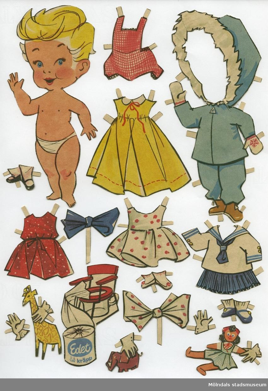 """Klippdocka med kläder och tillbehör från 1950-talet. Docka och kläder är märkta """"Laila"""" på baksidan - dockans namn. Dockan är urklippt ur tidning, och är också reklam för toalettpappret Edet Kräpp. Dockan föreställer ett litet barn, tecknat, med blont hår och iklädd blöja/underbyxa. Garderoben består av uteplagg (jacka med kapuschong och byxor), två kortare klänningar, en längre klänning, sjömanskostym med kjol, lekdräkt med korta ben, två scarves, tre par skor med strumpor, leksaker, samt en potta med tillhörande rulle Edet Kräpp. Docka och kläder har tidigare förvarats i samma kuvert som """"Diana"""" (MM 04575)."""