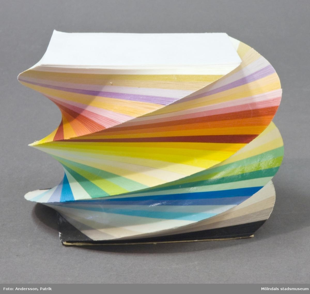 """Anteckningsblock, en så kallad """"Coloritspiral"""", tillverkad på Papyrus, Mölndal.Blocket består av kvadratiska blad, 9x9 cm, klistrade så att de utgör en randig spiralform i 32 färger. Coloritspiralen tillverkades för att användas vid, exempelvis konferenser."""