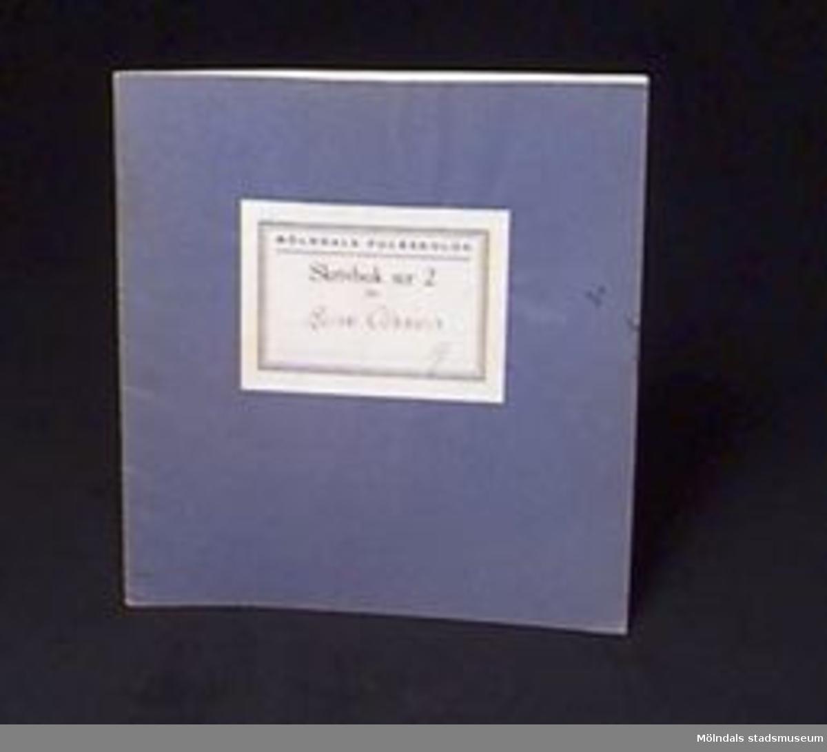 """Blå skrivbok med linjerade sidor. På omslaget en etikett med """"MÖLNDALS FOLKSKOLOR/Skrivbok n:r 2 för"""" samt skrivet med bläck: """"Rune Olsson A"""". Några sidor oskrivna.Givaren gick hela sin skoltid i Toltorpsskolan."""
