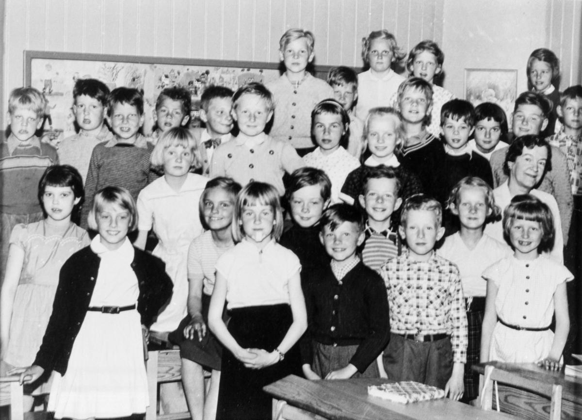 Gruppfoto med flickor och pojkar i klassrummet på Kvarnbyskolan (f.d. Centralskolan).