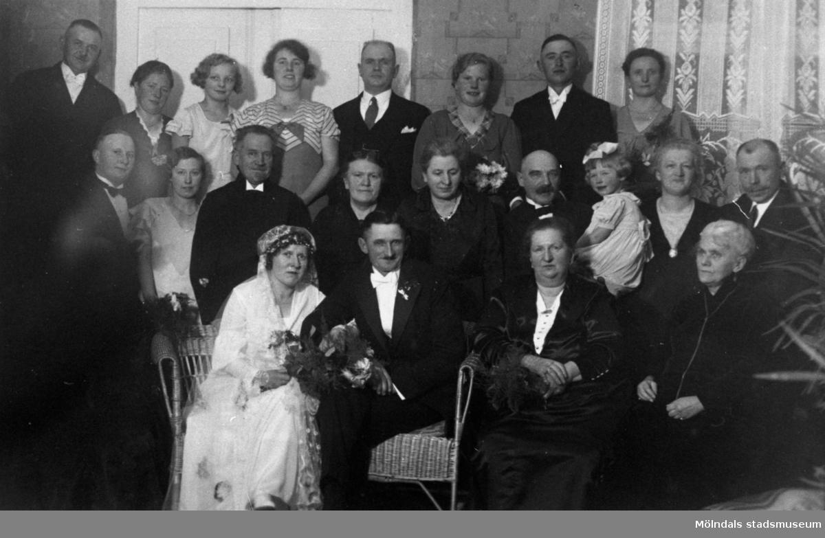 Bröllopsfoto med bröllopspar, släkt och vänner.