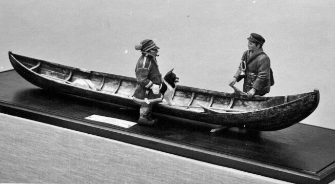 Forsbåt i modell, i den smäcka båten ligger åror, en stake, en postpåse. Vid sidan står en postförare och en same samt en gråhund. Postföraren är försedd med posthorn, postväska. Förlagan är använd vid 1880-talets slut i någon Norrlandsälv.