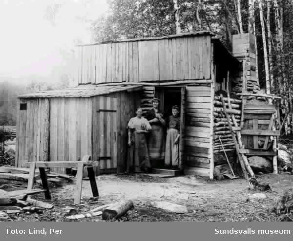 """Alby 1898. Arbetarbostad """"Kojor"""" enligt Linds anteckning. Framför byggnad en grupp på tre kvinnor."""