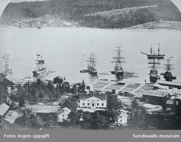 I förgrunden Svartviks herrgård i bildens mitt  hamnområdet med magasinbyggnader och uppläggningsplatser för timmer, i vattnet ligger cirka sju segelfartyg.