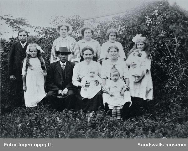 Enligt uppgift sågverksarbetarfamiljen Wikner i sin trädgård på Skönsmon. Längst till höger Juno, kusin Elin i randig klänning. Från vänster Valter, Jullan, Judith, Jenny och Johanna. Jenny for till Amerika 1903, hemma på besök 1913.
