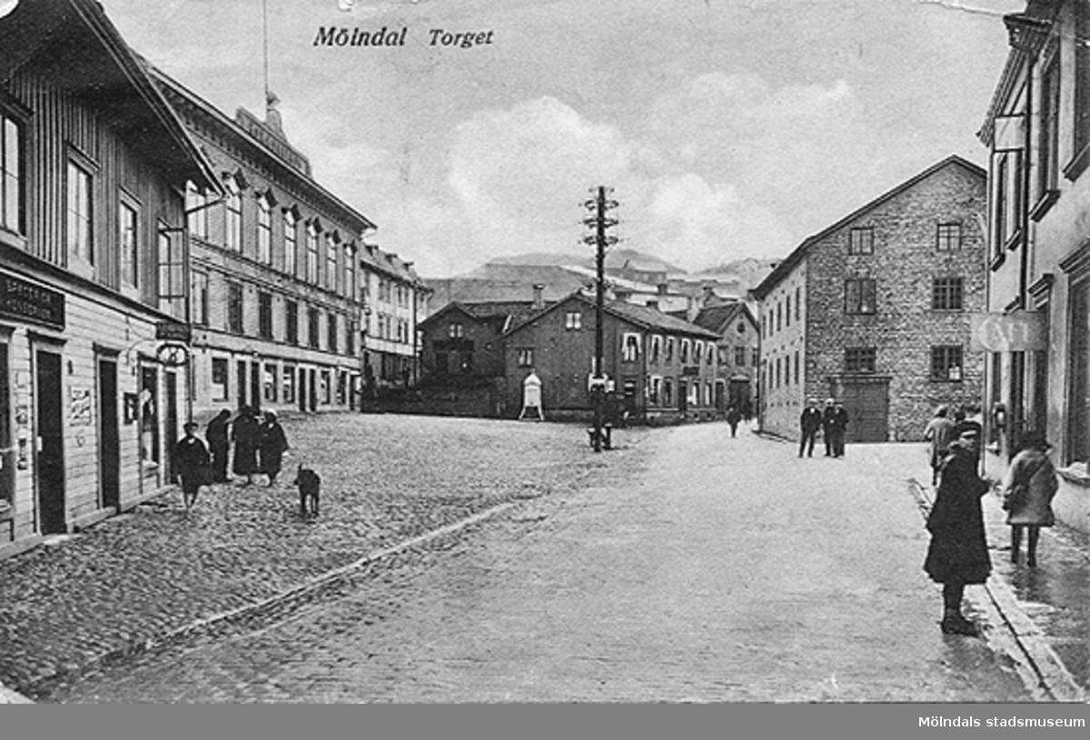 Vykort över Gamla torget (Mölndal Torget) sett från väster. Andra huset till vänster är Gamla stadshuset. Första huset till höger, med café-skylten, är Byggnad 213 på Kvarnbygatan 4.